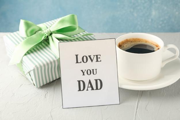 Tasse kaffee, geschenkbox mit grünem band und inschrift love you dad auf weißem tisch vor blauem hintergrund, platz für text