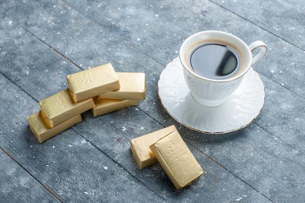 Tasse kaffee heiß und stark mit goldgeformter schokolade auf blauem schreibtisch, kaffeekakaogetränk heiß