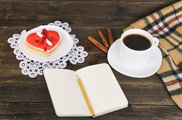 Tasse kaffee, herz formten plätzchen mit mitteilung, notizbuch, bleistift und kariertem plaid auf einem braunen holztisch