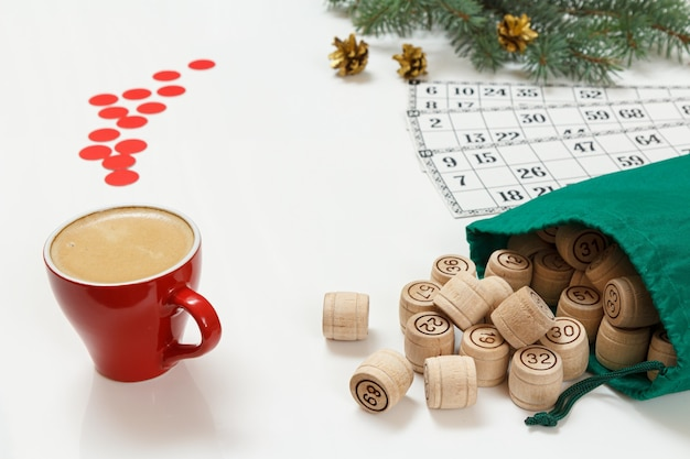 Tasse kaffee, hölzerne lottofässer mit grüner tüte und spielkarten