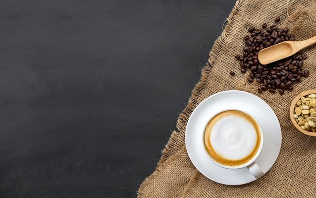 Tasse kaffee, holzlöffel und kaffeebohnen in einer schüssel