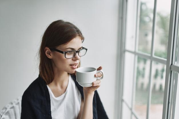Tasse kaffee in den händen einer frau, die in einem stuhl nahe dem fensterinneren sitzt