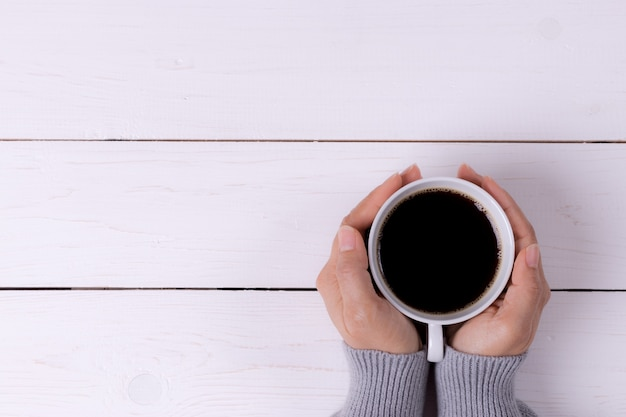Tasse kaffee in den weiblichen händen auf weißem holztisch