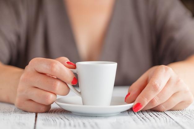 Tasse kaffee in der frauenhand auf tisch