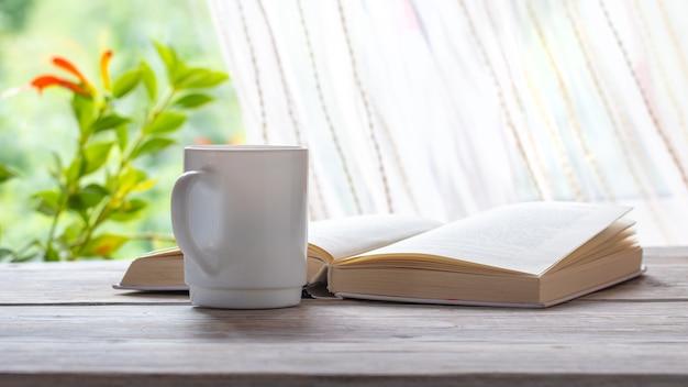 Tasse kaffee in der nähe eines offenen buches