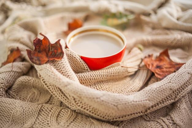 Tasse kaffee in einen beige wollpullover gewickelt
