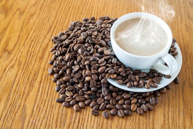 Tasse kaffee in einer weißen schale und in den kaffeebohnen auf holztisch