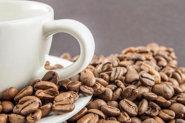 Tasse kaffee in einer weißen schale und in den kaffeebohnen