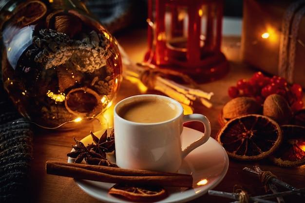 Tasse kaffee in festlichen dekorationen mit lichterketten einer fee