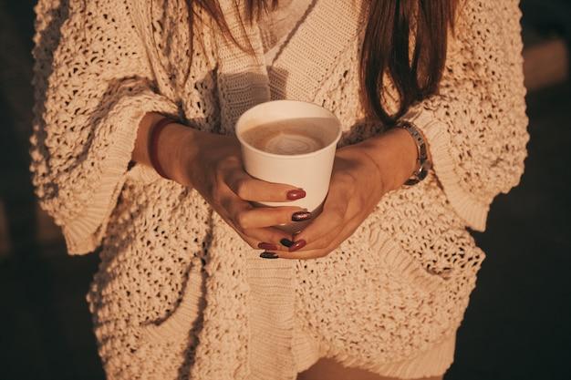 Tasse kaffee in händen. hände der frau, die papierschale eines kaffees halten.