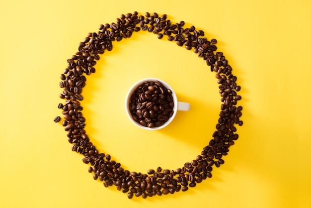 Tasse kaffee in kreisform kaffeebohnen auf gelbem hintergrund