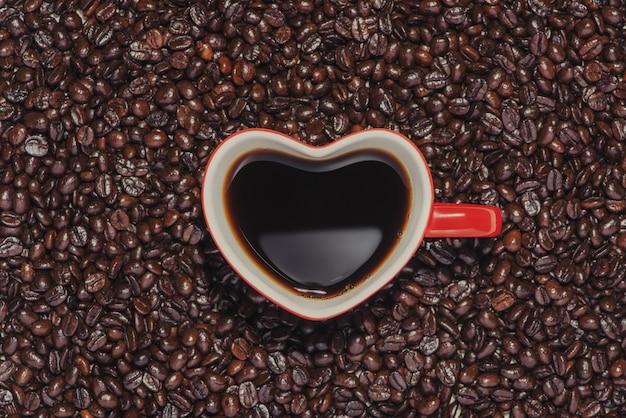 Tasse kaffee in roter herzform auf bohnenhintergrund