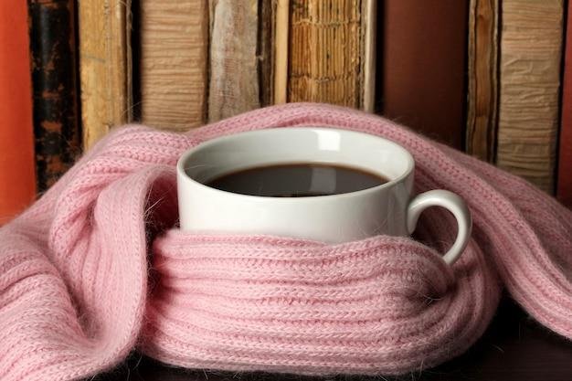 Tasse kaffee in schal auf büchern gewickelt
