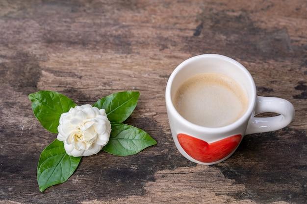 Tasse kaffee, jasminblüte auf holztisch
