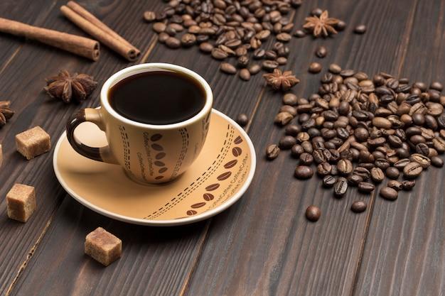 Tasse kaffee, kaffeebohnen auf den tisch gestreut. gewürze sternanis und braune zuckerstücke.