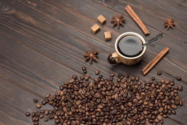 Tasse kaffee, kaffeebohnen auf den tisch gestreut.