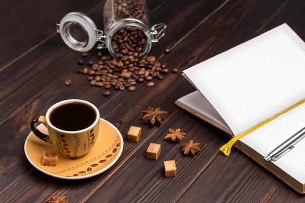 Tasse kaffee, kaffeebohnen im glas. notizbuch mit stift öffnen. auf dem tisch gewürze sternanis und stücke braunen zuckers.