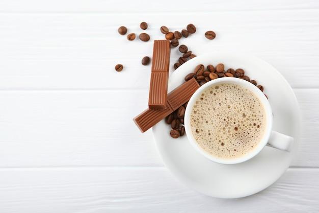 Tasse kaffee kaffeebohnen und schokolade auf dem tisch hautnah