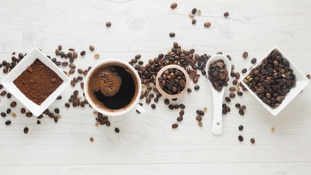 Tasse kaffee; kaffeepulver und kaffeebohnen in einer reihe auf dem schreibtisch angeordnet