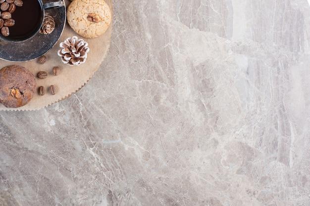 Tasse kaffee, kekse, kaffeebohnen und ein tannenzapfen auf marmor.