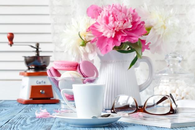 Tasse kaffee, kekse und blumen auf dem tisch
