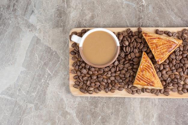Tasse kaffee, kekse und kaffeebohnen auf holzbrett. foto in hoher qualität