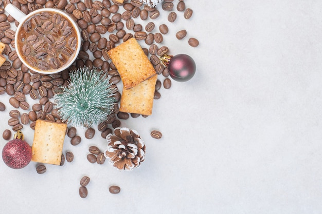 Tasse kaffee, kekse und weihnachtskugeln auf steinoberfläche.