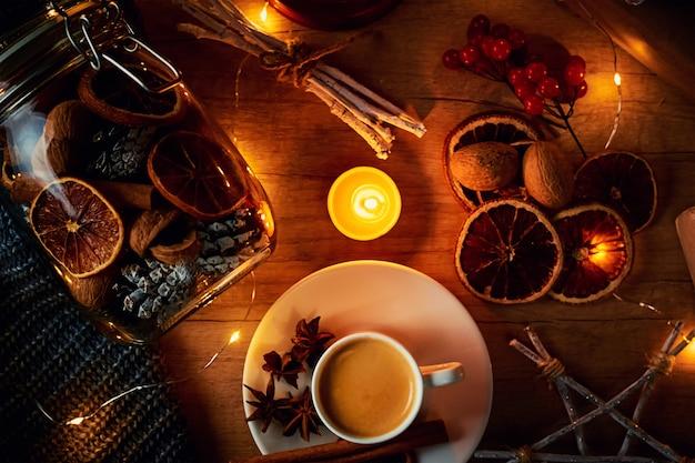 Tasse kaffee, kerzen und dekorationen mit einer girlande beleuchtet, draufsicht