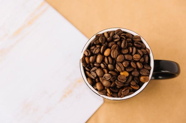 Tasse kaffee körner in der nähe von blatt