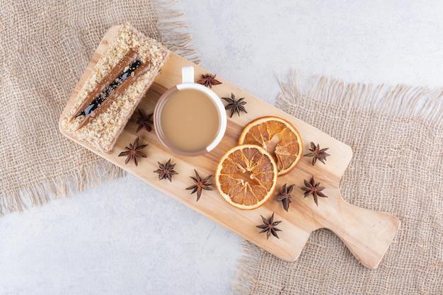 Tasse kaffee, kuchen und orangenscheiben auf holzbrett. foto in hoher qualität