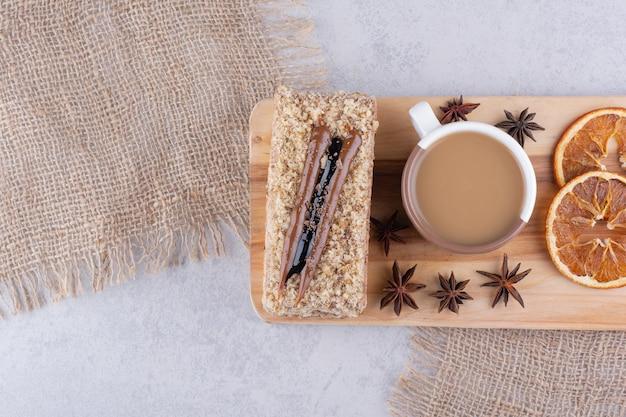 Tasse kaffee, kuchen und orangenscheiben auf holzbrett.