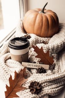 Tasse kaffee, kürbis, getrocknetes herbstlaub am fenster.