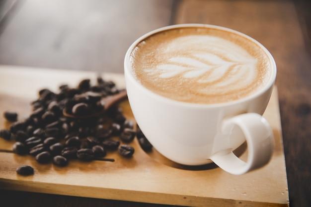 Tasse kaffee latte auf hölzerner tabelle im kaffeestubecafé