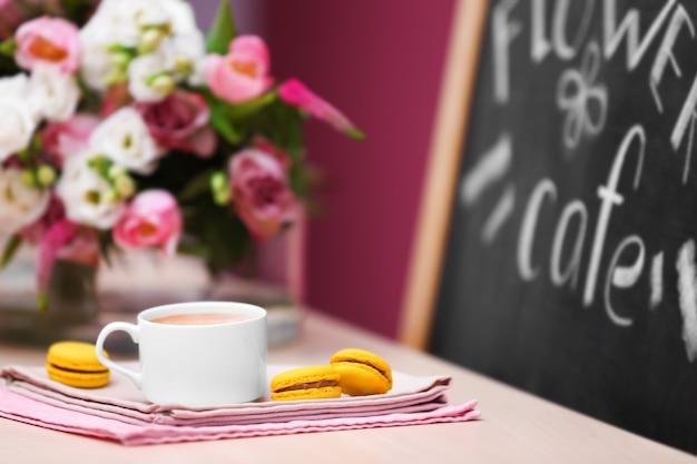 Tasse kaffee, leckerer kuchen und schöner blumenstrauß im café