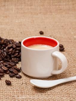 Tasse kaffee, löffel und geröstete kaffeebohnen auf sackleinen.
