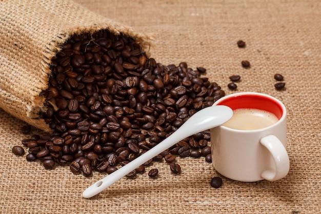 Tasse kaffee, löffel und geröstete kaffeebohnen in einem leinensack auf sackleinenhintergrund.