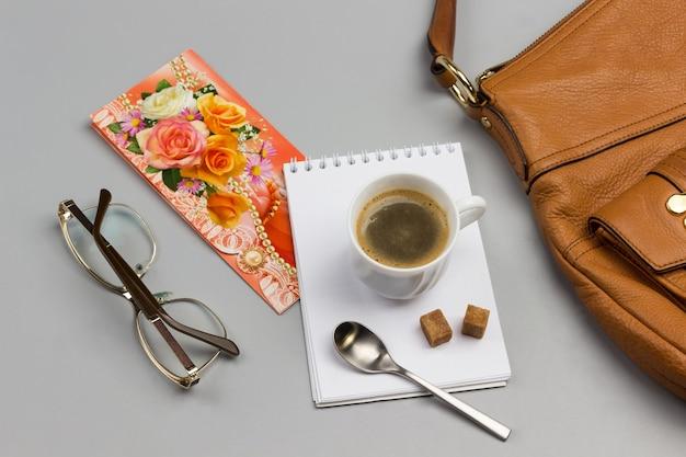 Tasse kaffee, löffel und zuckerwürfel auf notebook mit brille, postkarte und brauner handtasche auf dem tisch.