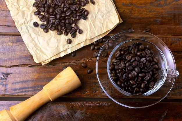 Tasse kaffee lokalisiert mit den gebratenen und frischen bohnen auf rustikalem holztisch
