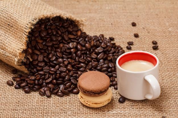 Tasse kaffee, makronen und geröstete kaffeebohnen in einem leinensack auf sackleinen.