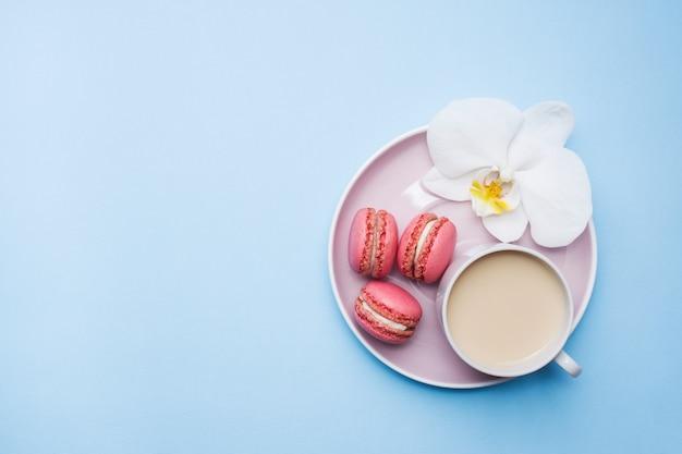 Tasse kaffee-makronenplätzchen auf blauem pastellhintergrund mit flacher lage