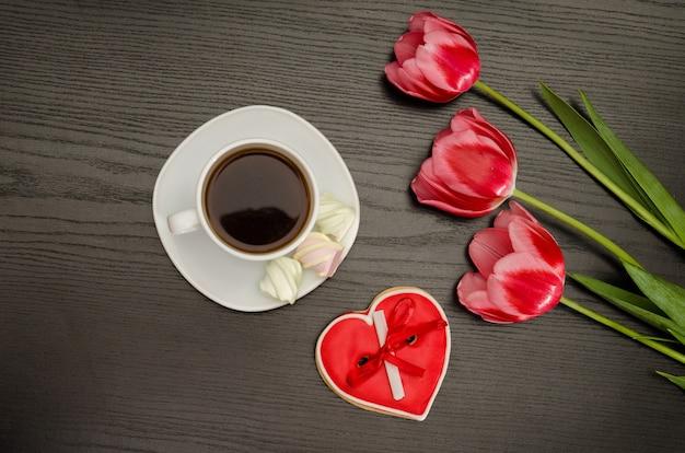 Tasse kaffee, marshmallows und lebkuchen in herzform, drei rosa tulpen. schwarzer hintergrund.
