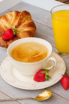 Tasse kaffee mit beeren und frischem saft zum frühstück