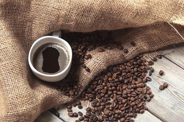 Tasse kaffee mit bohnen auf tabelle