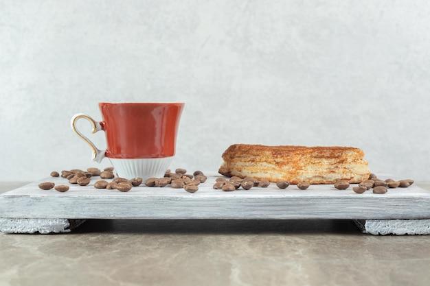 Tasse kaffee mit bohnen und gebäck auf holzbrett.