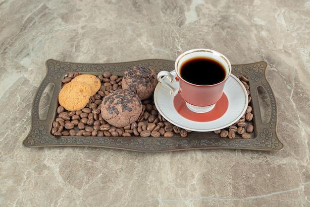 Tasse kaffee mit bohnen und keksen auf teller