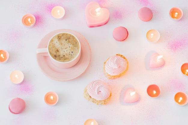 Tasse kaffee mit brennenden kerzen auf rosa gemaltem papier