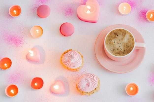 Tasse kaffee mit brennenden kerzen auf rosa lackierter papieroberfläche