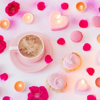 Tasse kaffee mit brennenden kerzen und rosen auf rosa gestrichenem papier