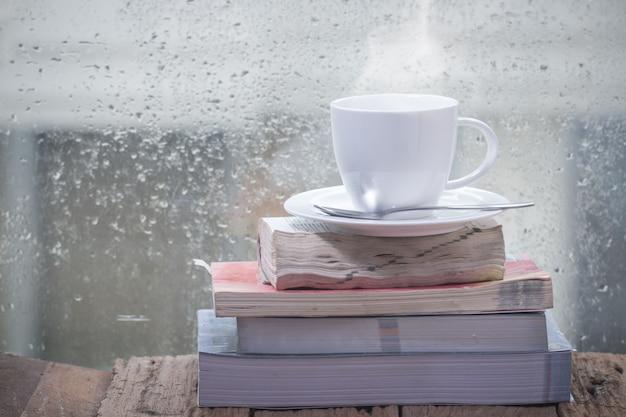 Tasse kaffee mit buch an einem regnerischen tag