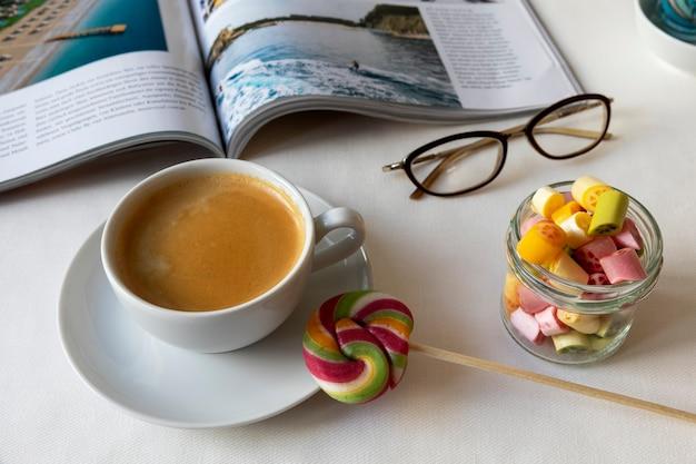 Tasse kaffee mit bunten lutscherbonbons in einem glasgefäß geöffnete zeitschrift